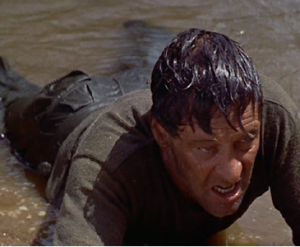 William Holden intenta destruir el puente.